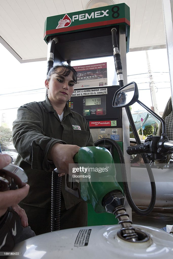 An attendant fills the tank of a motorcycle with gasoline at a Pemex station in Mexico City, Mexico, on Tuesday, Jan. 8, 2013. Mexico's government is speeding up the removal of subsidies on gasoline and increasing local unleaded gasoline prices by 11 centavos in January, according to the Finance Ministry. Photographer: Susana Gonzalez/Bloomberg via Getty Images