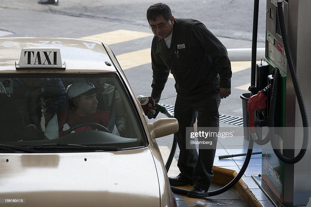 An attendant fills the tank of a taxi with gasoline at a Pemex station in Mexico City, Mexico, on Tuesday, Jan. 8, 2013. Mexico's government is speeding up the removal of subsidies on gasoline and increasing local unleaded gasoline prices by 11 centavos in January, according to the Finance Ministry. Photographer: Susana Gonzalez/Bloomberg via Getty Images