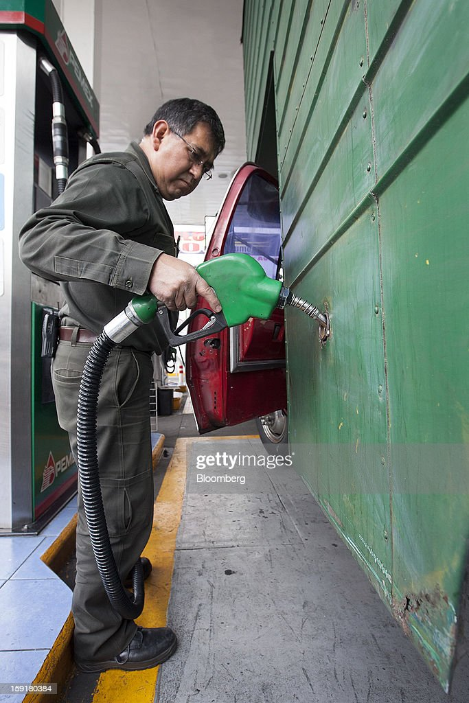 An attendant fills the tank of a truck with gasoline at a Pemex station in Mexico City, Mexico, on Tuesday, Jan. 8, 2013. Mexico's government is speeding up the removal of subsidies on gasoline and increasing local unleaded gasoline prices by 11 centavos in January, according to the Finance Ministry. Photographer: Susana Gonzalez/Bloomberg via Getty Images