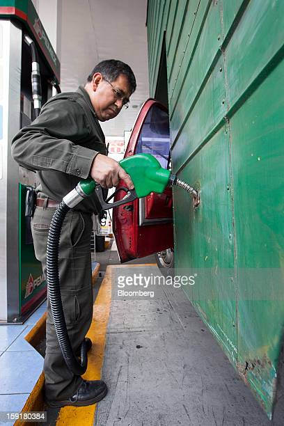 An attendant fills the tank of a truck with gasoline at a Pemex station in Mexico City Mexico on Tuesday Jan 8 2013 Mexico's government is speeding...