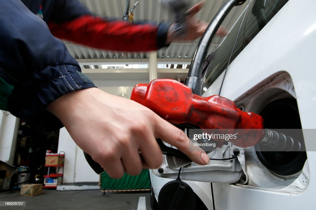 An attendant fills the tank of a vehicle with a fuel pump at a gas station in Tokyo, Japan, on Friday, Jan. 25, 2013. Japan's consumer prices fell for the seventh time in eight months, underscoring the risk that the central bank may struggle to reach a 2 percent inflation target unless it implements new easing measures earlier than planned. Photographer: Kiyoshi Ota/Bloomberg via Getty Images