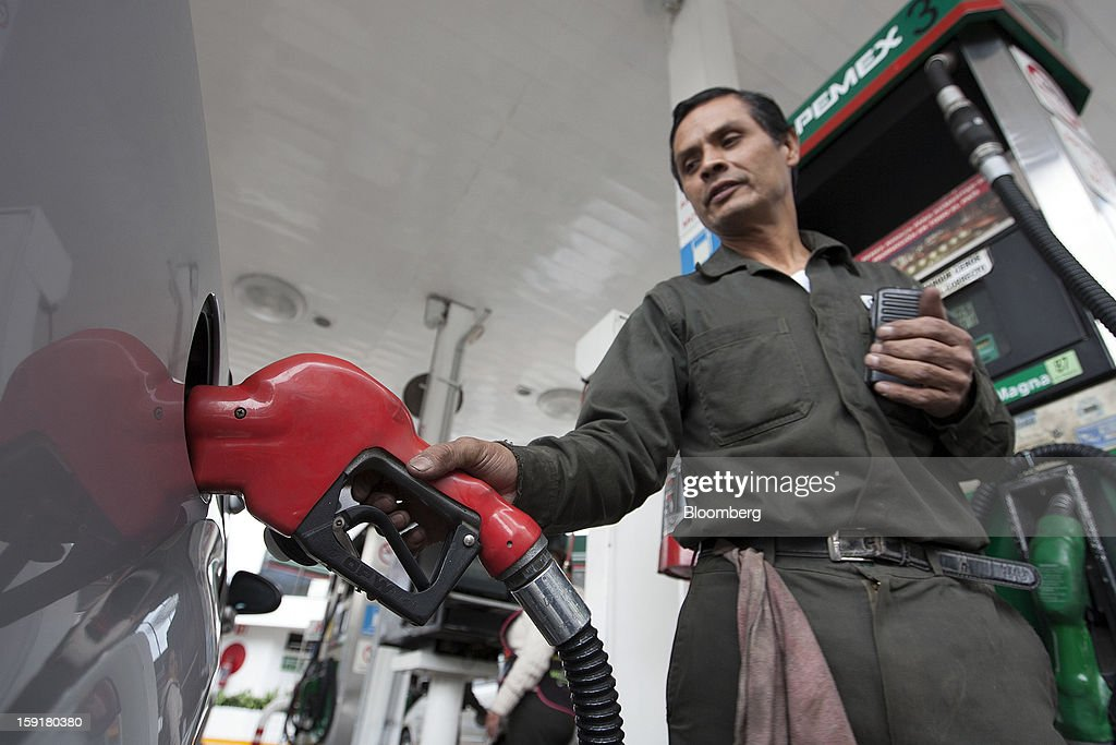 An attendant fills the tank of a vehicle with gasoline at a Pemex station in Mexico City, Mexico, on Tuesday, Jan. 8, 2013. Mexico's government is speeding up the removal of subsidies on gasoline and increasing local unleaded gasoline prices by 11 centavos in January, according to the Finance Ministry. Photographer: Susana Gonzalez/Bloomberg via Getty Images