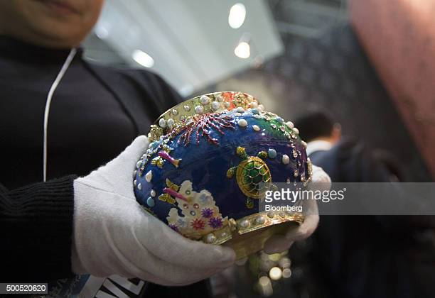 An attendant holds a cinerary urn manufactured by Swarovski at the Life Ending Industry Expo in Tokyo Japan on Tuesday Dec 8 2015 The exhibition of...