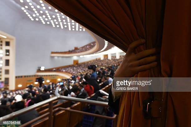 An attendant holds a curtain at an entrance during the opening session of the National People's Congress in the Great Hall of the People in Beijing...