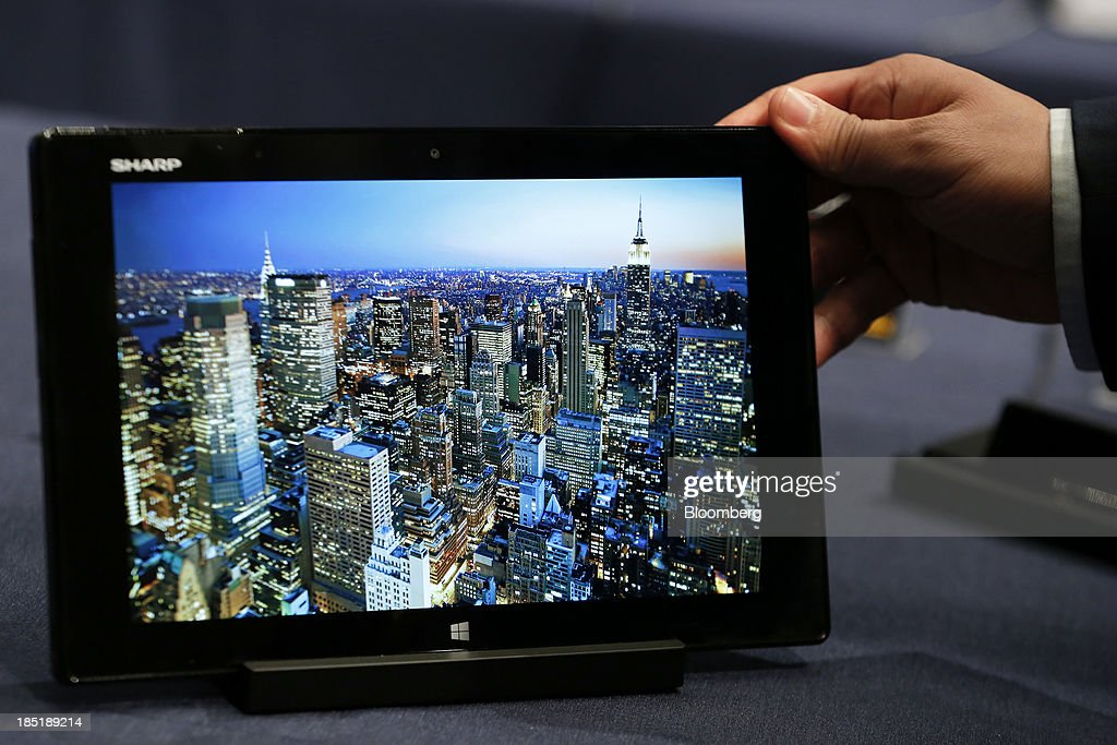 An attendant holds a Sharp Corp. Mebius Pad tablet, running Microsoft Corp.'s Windows 8.1 operating system, during a launch event for the operating system in Tokyo, Japan, on Friday, Oct. 18, 2013. Microsoft Chief Executive Officer Steve Ballmer, who will be retiring within a year, said the company is still working to make sure that the personal computer remains relevant as 'the device of choice.' Photographer: Kiyoshi Ota/Bloomberg via Getty Images