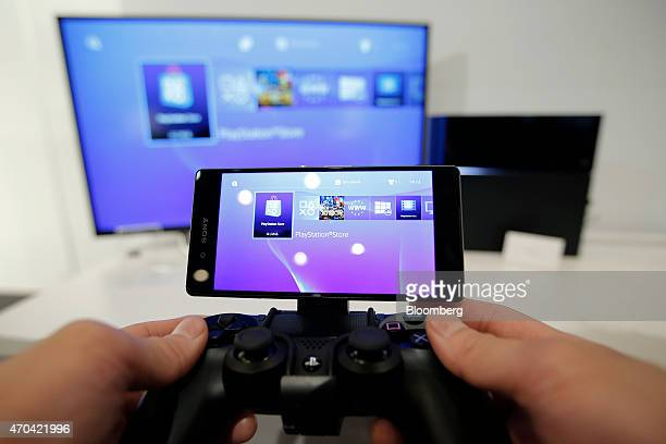 An attendant holds the a PlayStation 4 videogame console controller attached to a Sony Corp Xperia Z4 smartphone manufactured by Sony Mobile...