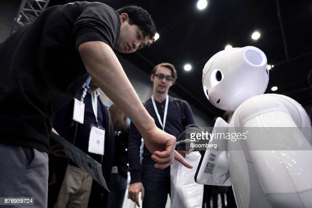 An attendant left demonstrates an application on a SoftBank Group Corp Pepper humanoid robot at the SoftBank Robot World 2017 in Tokyo Japan on...