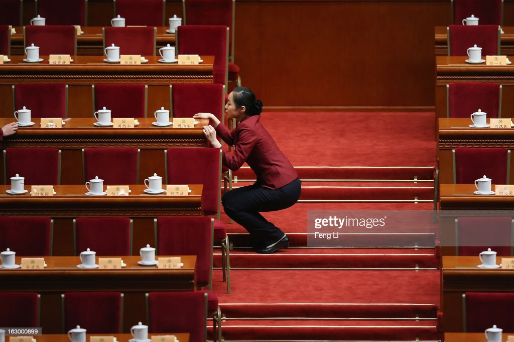 An attendant looks at whether teacups are placed neatly before the opening session of the Chinese People's Political Consultative Conference in Beijing's Great Hall of the People on March 3, 2013 in Beijing, China. Over 2,000 members of the 12th National Committee of the Chinese People's Political Consultative, a political advisory body, are attending the annual session, during which they will discuss the development of China.