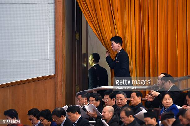 An attendant opens a curtain as a man leaves during the opening ceremony of the National People's Congress at the Great Hall of the People in Beijing...