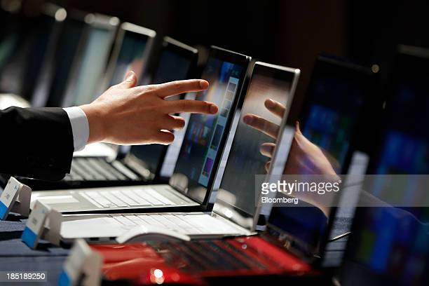 An attendant points towards a laptop computer running Microsoft Corp's Windows 81 operating system displayed during a launch event for the operating...