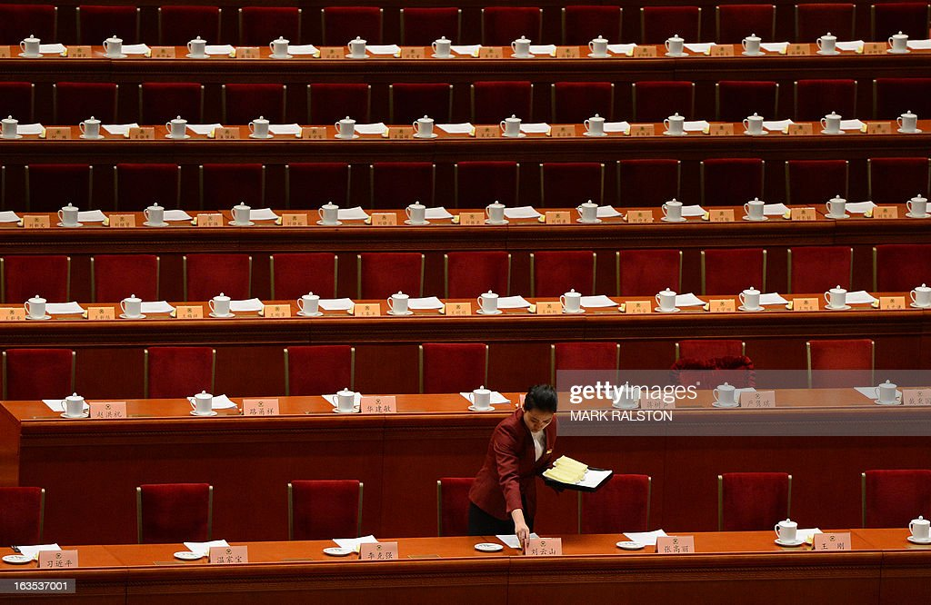 An attendant prepares for the arrival of delegates during the closing session of the Chinese People's Political Consultative Conference (CPPCC) at the Great Hall of the People in Beijing on March 12, 2013. Thousands of delegates from across China met this week to seal a power transfer to new leaders whose first months running the Communist Party have pumped up expectations with a deluge of propaganda. AFP PHOTO/Mark RALSTON