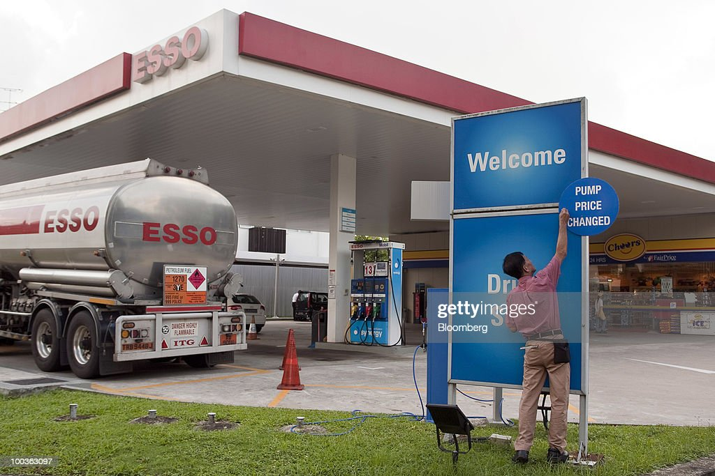 An attendant puts up a sign at an Esso gas station in Singapore, on Monday, May 24, 2010. Singapore's consumer prices rose at the fastest pace in 14 months in April as an accelerating economy and a booming labor market boosted housing and transportation costs. Photographer: Charles Pertwee/Bloomberg via Getty Images