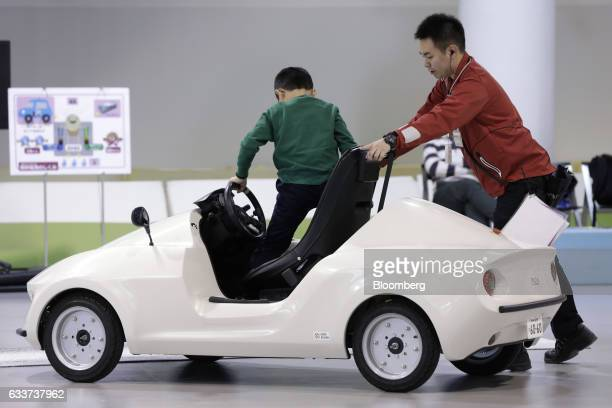 An attendant right assists a child to step out of a Modi Corp Pius micro electric vehicle during a driving experience course inside the Ride Studio...