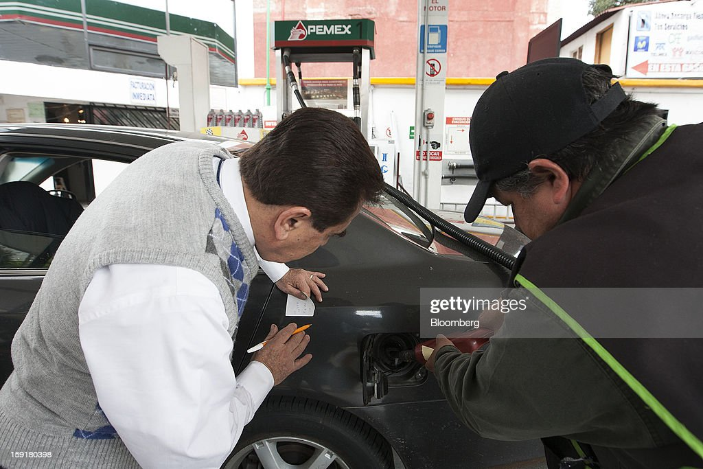 An attendant, right, fills the tank of a customer's vehicle with gasoline as he looks on at a Pemex station in Mexico City, Mexico, on Tuesday, Jan. 8, 2013. Mexico's government is speeding up the removal of subsidies on gasoline and increasing local unleaded gasoline prices by 11 centavos in January, according to the Finance Ministry. Photographer: Susana Gonzalez/Bloomberg via Getty Images