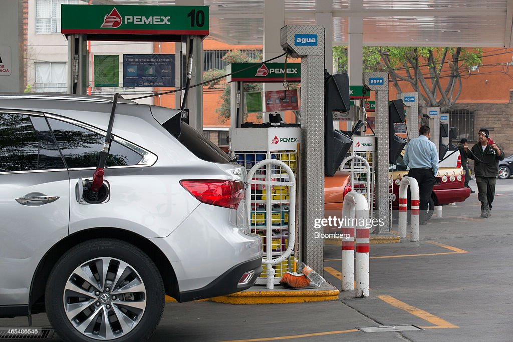 An attendant right helps a customer at a Petroleos Mexicanos gas station in Mexico City Mexico on Friday March 6 2015 Oil contracts worth more than...