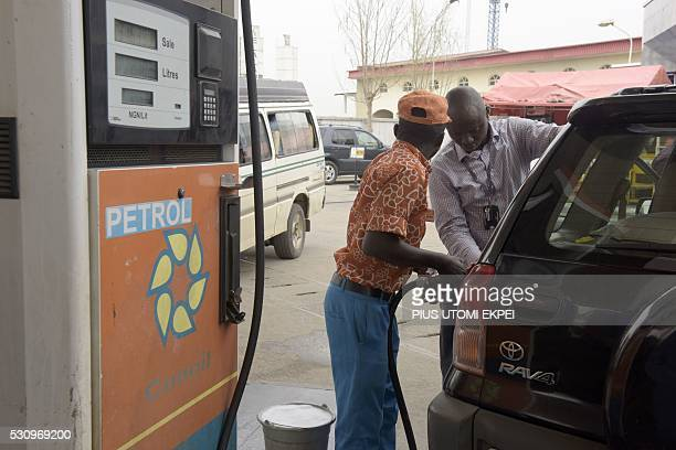 An attendant sells fuel to a motorist at a filling station in Lagos on May 12 2016 Nigeria hiked the price of petrol on May 11 2016 after months of...