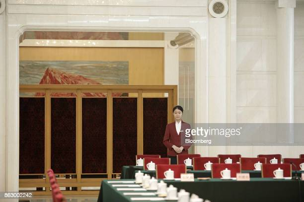 An attendant stands behind rows of tables inside the Great Hall of the People during the 19th National Congress of the Communist Party of China in...