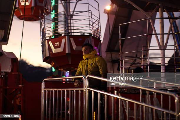 An attendant stands by a ferris wheel as visitors enjoy the attractions at the Nottingham Goose Fair in the Forest Recreation Ground on October 7...