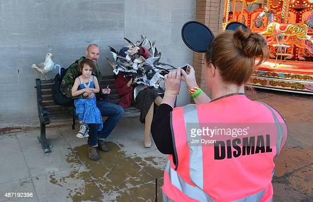 An attendant takes a photo of visitors beside a sculture by Banksy depicting a woman being attacked by seagulls as Banksy's Dismaland Bemusement Park...