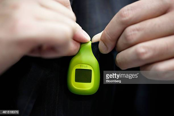 An attendant wears Fitbit Inc's Fitbit Zip wireless activity tracker for a photograph at the Wearable Expo in Tokyo Japan on Wednesday Jan 14 2015...