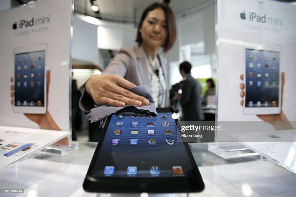 An attendant wipes an Apple Inc. iPad Mini in an arranged photograph at a KDDI Corp. store in Tokyo, Japan, on Friday, Nov. 30, 2012. The iPad Mini went on sale at KDDI and Softbank Corp. stores in Japan today. Photographer: Kiyoshi Ota/Bloomberg via Getty Images