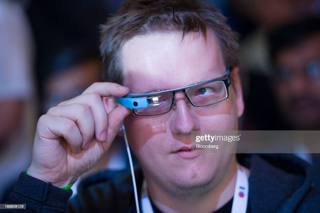 An attendee adjusts his Google Project Glass glasses during the Google I/O Annual Developers Conference in San Francisco, California, U.S., on Wednesday, May 15, 2013. Google Inc. introduced a subscription music-streaming service, one of several product updates to be unveiled at a developer meeting this week as the search provider seeks to attract more users and advertisers. Photographer: David Paul Morris/Bloomberg via Getty Images