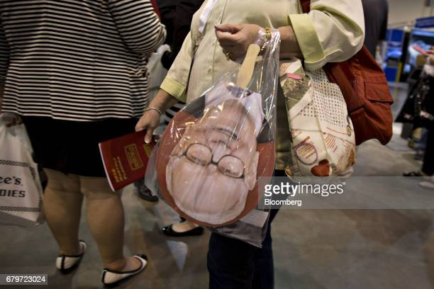 An attendee carries a bag with a sign in the likeness of Warren Buffett chairman and chief executive officer of Berkshire Hathaway Inc on the exhibit...