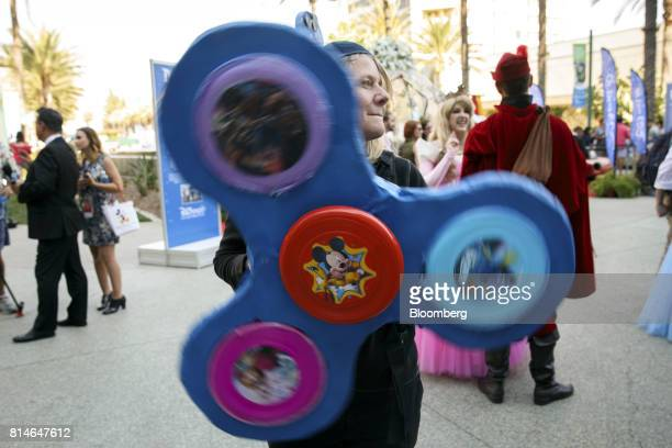 An attendee carries a giant fidget spinner featuring Mickey Mouse at the D23 Expo 2017 in Anaheim California US on Friday July 14 2017 Burbank...