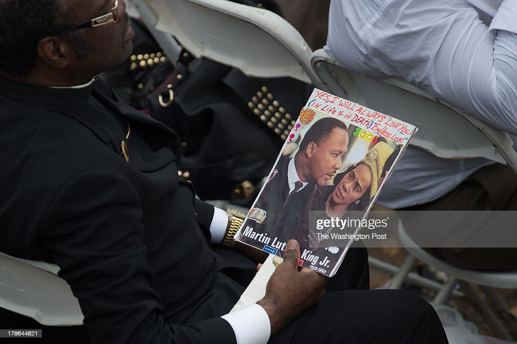 An attendee carries a photo of Martin Luther King, Jr., and Coretta Scott King at the 50th Anniversary March on Washington at the Lincoln Memorial in Washington, D.C., on Wednesday, August 28, 2013.