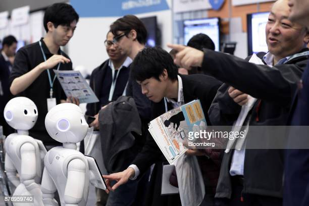 An attendee center tries out an application on a SoftBank Group Corp Pepper humanoid robot at the SoftBank Robot World 2017 in Tokyo Japan on Tuesday...