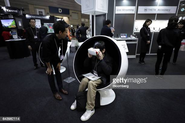 An attendee center wears a virtual reality headset with a smartphone installed to view the images taken with Ricoh Co Theta 360degree spherical...