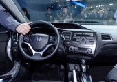 An attendee checks the steering wheel of new 2013 Honda Civic sedan during the Los Angeles Auto show on November 29 2012 in Los Angeles California...