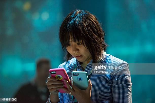 An attendee checks two Apple Inc iPhones prior to the start of the Google I/O Annual Developers Conference in San Francisco California US on Thursday...