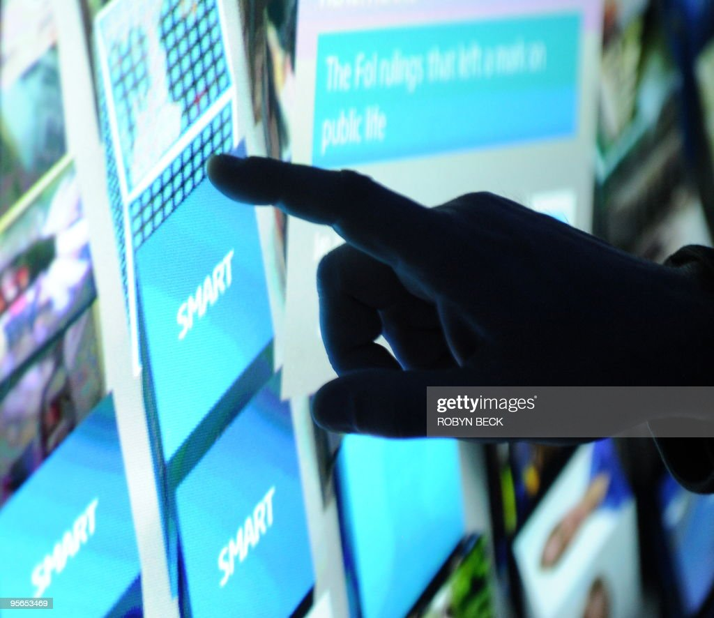 An attendee chooses internet content from a computer powered by the new Intel Core i7 processor and displayed on a prototype optical touch rear projection double high screen at the Intel booth at the 2010 International Consumer Electronics Show on January 8, 2010 in Las Vegas. CES, the world's largest annual consumer technology tradeshow, runs from January 7-10. AFP PHOTO/Robyn Beck