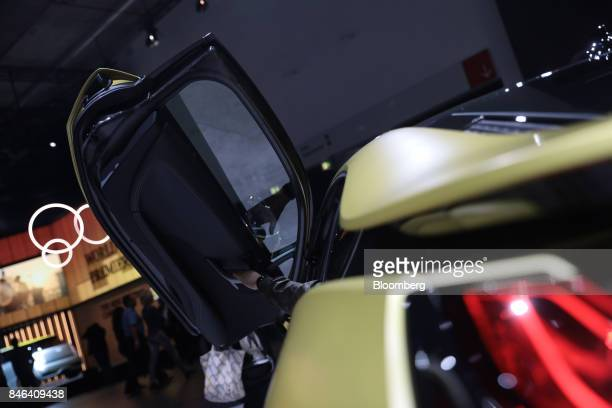 An attendee closes the butterfly door of a BMW i8 electric automobile manufactured by Bayerische Motoren Werke AG during the second media preview day...