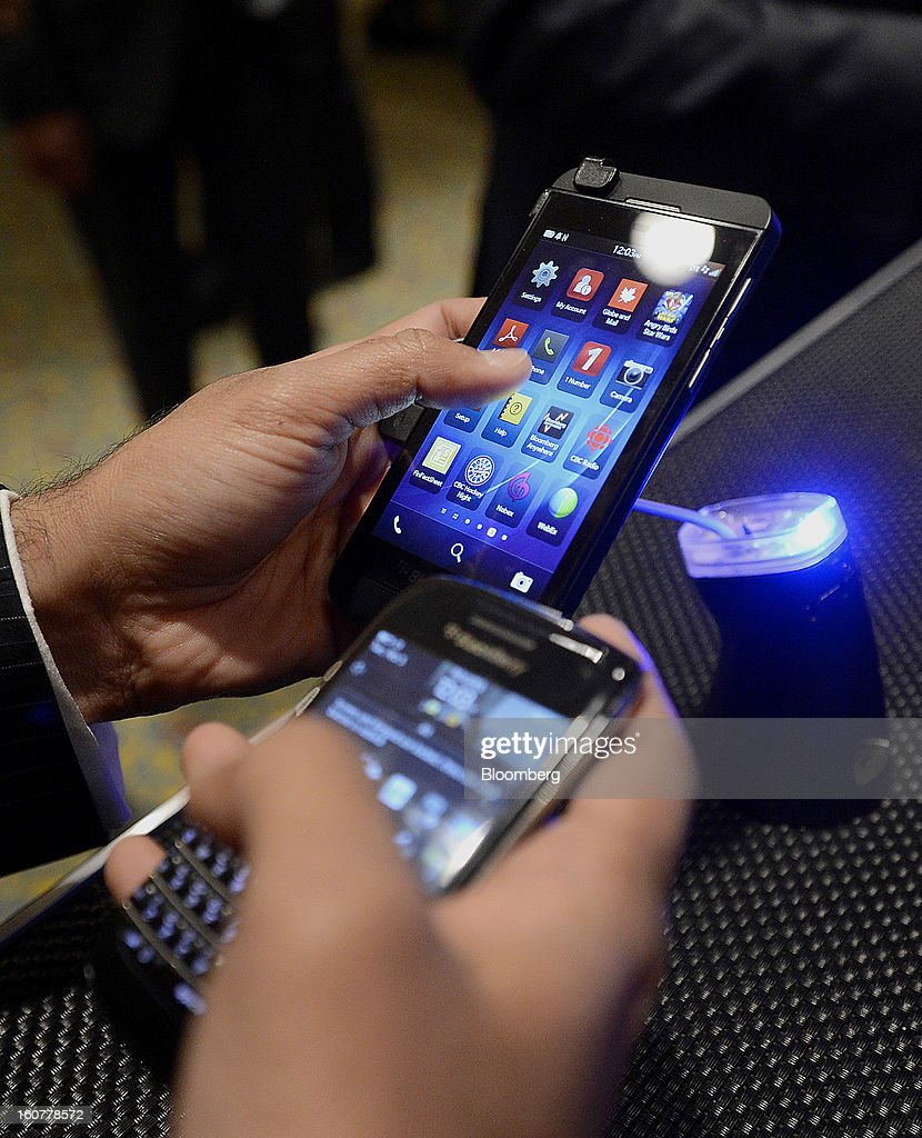 "An attendee compares the BlackBerry Z10, top left, with another device during an event at the Empire Club of Canada in Toronto, Ontario, Canada, on Tuesday, Feb. 5, 2013. Thorsten Heins, chief executive officer of BlackBerry, said early sales of the Z10 smartphone are ""encouraging"" and that users are switching from other platforms. Photographer: Aaron Harris/Bloomberg via Getty Images"