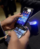 An attendee compares the BlackBerry Z10 top left with another device during an event at the Empire Club of Canada in Toronto Ontario Canada on...