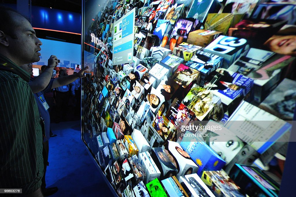 An attendee considers which internet content to choose via a computer powered by the new Intel Core i7 processor displayed on a prototype optical touch rear projection double high screen at the Intel booth at the 2010 International Consumer Electronics Show on January 8, 2010 in Las Vegas. CES, the world's largest annual consumer technology tradeshow, runs from January 7-10. AFP PHOTO/Robyn Beck