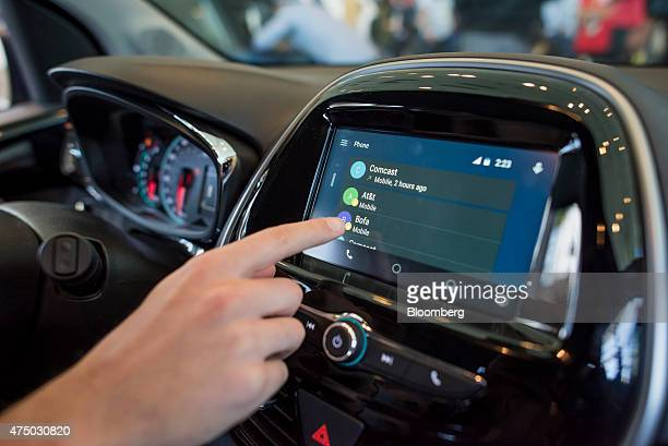 An attendee demonstrates Android Auto in a Chevrolet Corp Spark car during the Google I/O Annual Developers Conference in San Francisco California US...