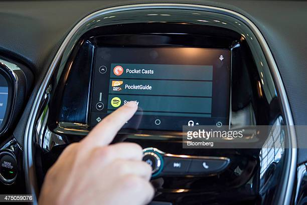 An attendee demonstrates Google Inc Android Auto in a Chevrolet Corp Spark car during the Google I/O Annual Developers Conference in San Francisco...