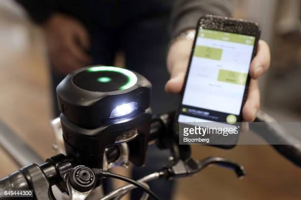 An attendee demonstrates the CycleLabs Solutions Inc SmartHalo smart biking device and mobile application for a photograph at a SoftBank Corp Style...
