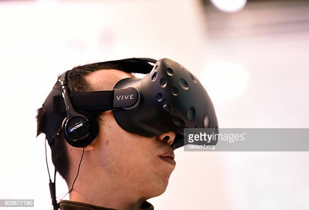 An attendee demonstrates the HTC Vive virtual reality headset during the 2016 Consumer Electronics Show in Las Vegas Nevada US on Wednesday Jan 6...