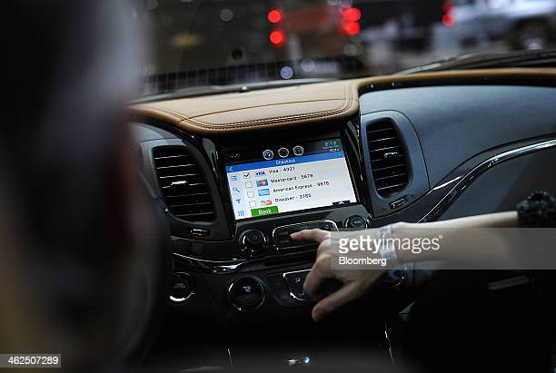 An attendee demonstrates the OnStar Corp 4G LTE dash system on a General Motors Co Chevrolet Impala vehicle during the 2014 North American...
