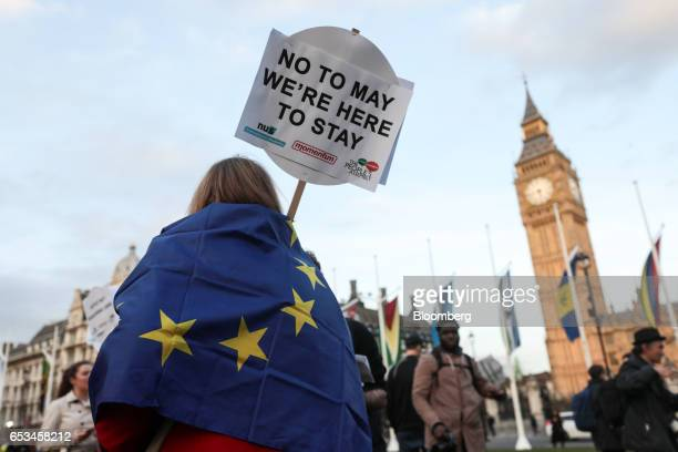 An attendee draped in a European Union flag holds a placard with the message 'No to May we're here to stay' at a demonstration in support of EU...