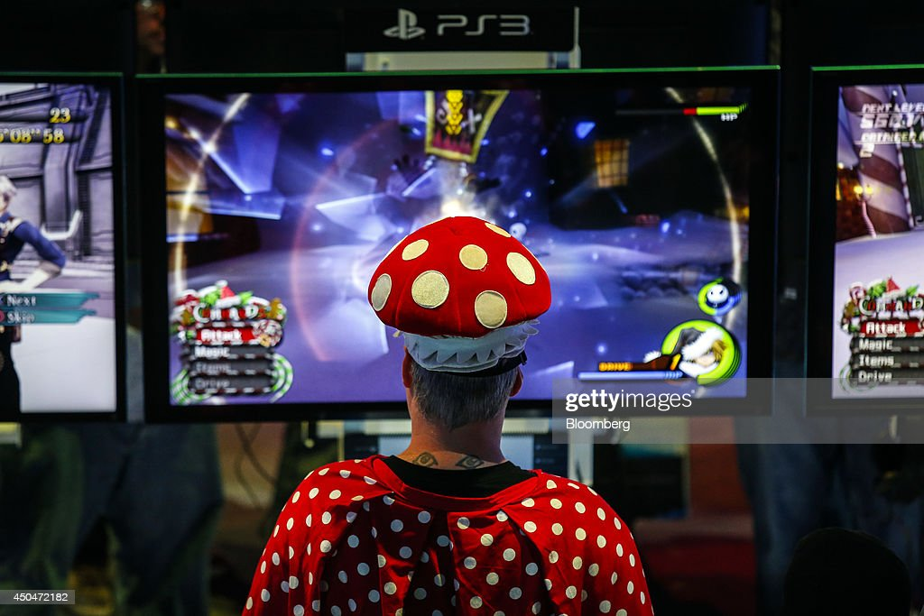 An attendee dressed as a Nintendo Co. character plays a video game on Sony PlayStation 3 (PS3) console during the E3 Electronic Entertainment Expo in Los Angeles, California, U.S., on Wednesday, June 11, 2014. E3, a trade show for computer and video games, draws professionals to experience the future of interactive entertainment as well as to see new technologies and never-before-seen products. Photographer: Patrick T. Fallon/Bloomberg via Getty Images