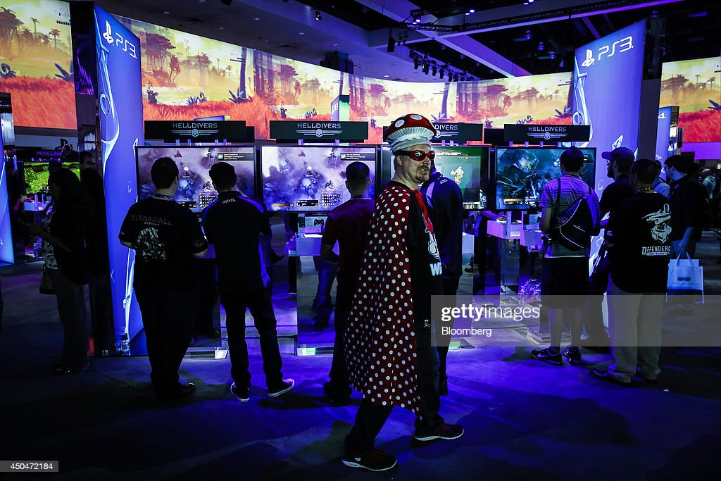 An attendee dressed as a Nintendo Co. character walks past demos of video games on Sony PlayStation 3 (PS3) consoles during the E3 Electronic Entertainment Expo in Los Angeles, California, U.S., on Wednesday, June 11, 2014. E3, a trade show for computer and video games, draws professionals to experience the future of interactive entertainment as well as to see new technologies and never-before-seen products. Photographer: Patrick T. Fallon/Bloomberg via Getty Images