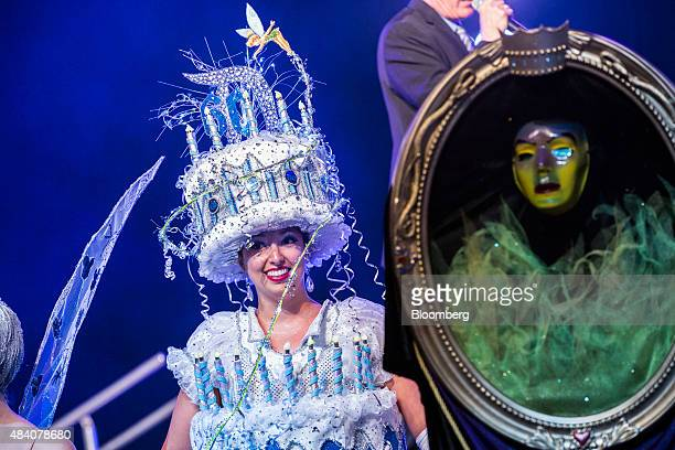 An attendee dressed in a Walt Disney Co's Disneyland 60th anniversary birthday cake costume smiles to the crowd during a costume contest at the D23...