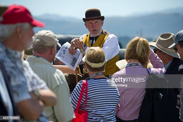 An attendee dressed in period clothing speaks to other attendees during the 2014 Pebble Beach Concours d'Elegance in Pebble Beach California US on...