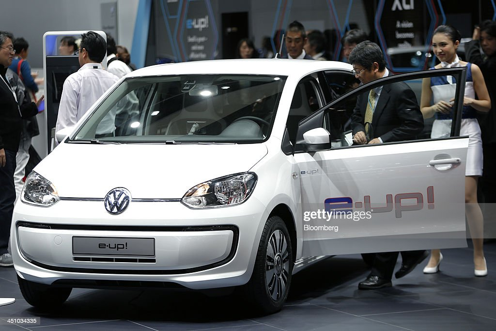 An attendee examines a Volkswagen AG (VW) e-Up! electric vehicle on display at the 43rd Tokyo Motor Show 2013 in Tokyo, Japan, on Thursday, Nov. 21, 2013. The autoshow will be open to the public from Nov. 23 to Dec. 1 at the Tokyo International Exhibition Center, also known as the Tokyo Big Sight. Photographer: Kiyoshi Ota/Bloomberg via Getty Images