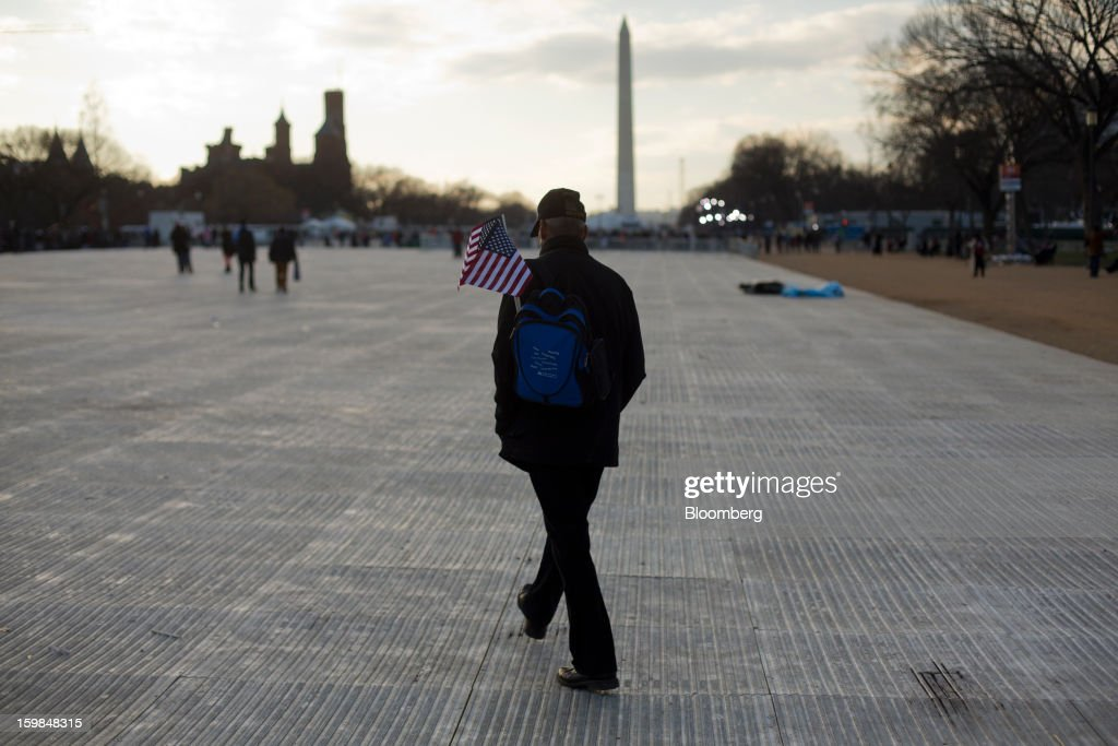 An attendee holding an American flag walks through the National Mall during the U.S. presidential inauguration in Washington, D.C., U.S., on Monday, Jan. 21, 2013. A crowd estimated by police to be as large as 700,000, including warmly dressed women with American flags stuck in their hair, a smattering of celebrities and many Republicans, gathered today to witness President Barack Obama take his second oath of office on the steps of the U.S. Capitol. Photographer: Victor J. Blue/Bloomberg via Getty Images